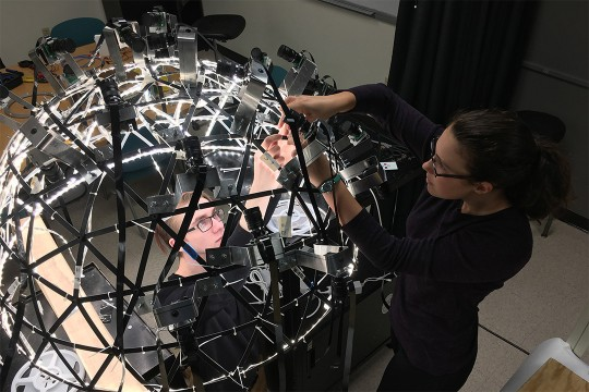 Students work on dome-shaped imaging system.