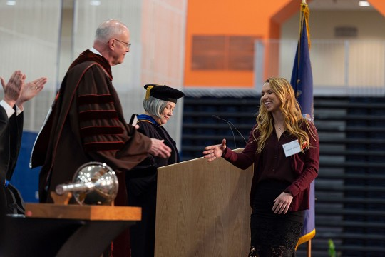 Student reaches out to skae President Munson's hand while walking across a stage.