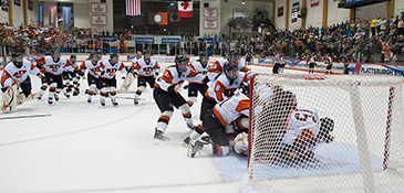 Women's Hockey team storming the goalie after winning