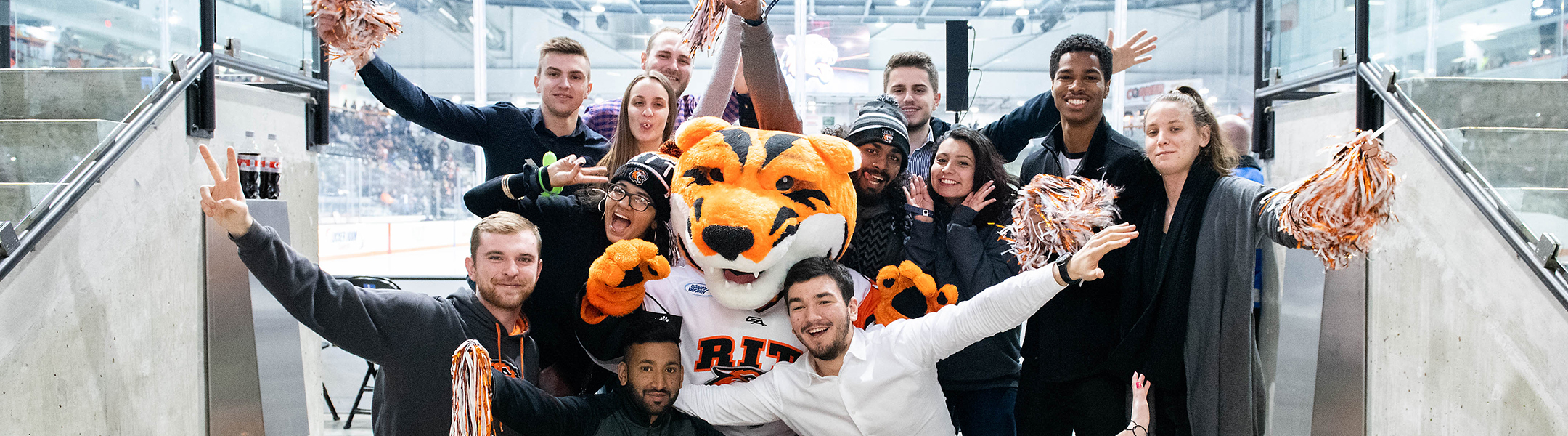 Students posing for a photograph outside of the RIT hockey arena
