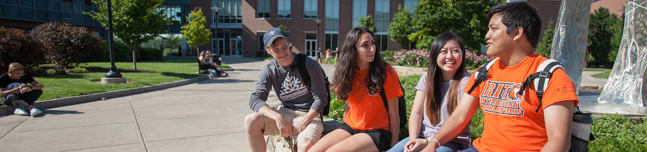 Students sitting on a brick wall in a courtyard on a sunny day wearing orange RIT shirts
