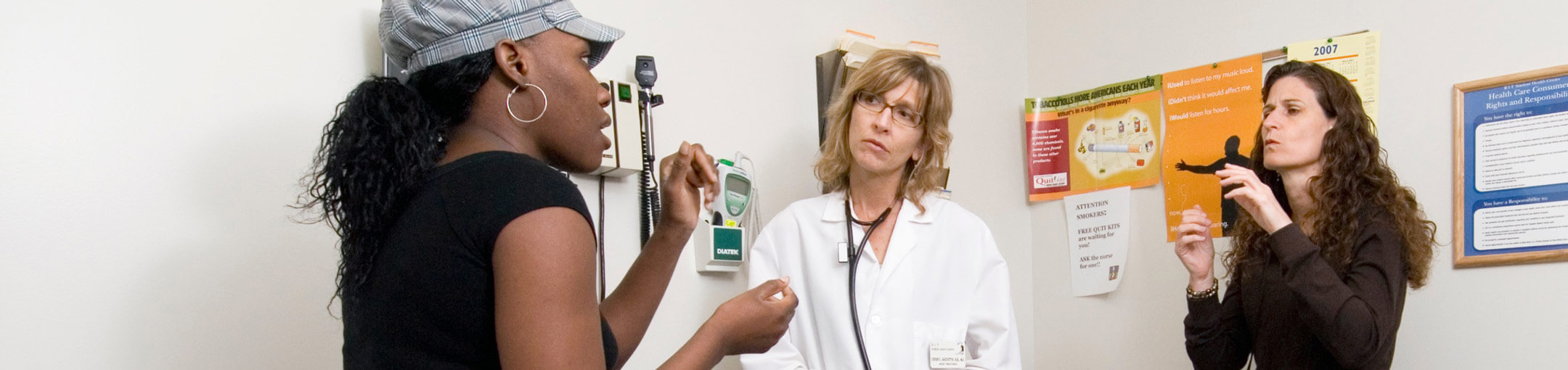 A patient communicating with a doctor in an exam room with an interpreter.