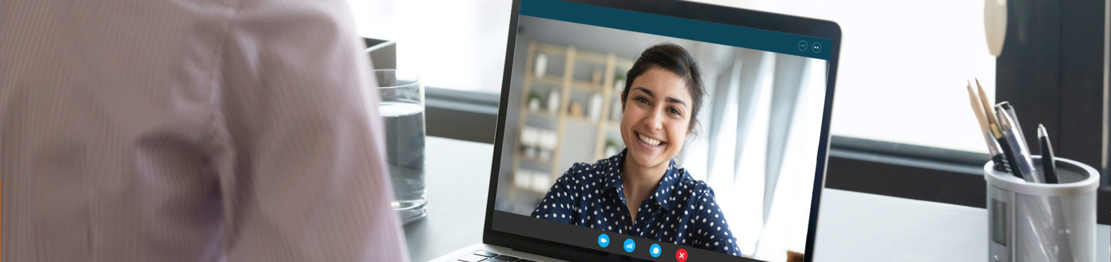 A person looking at a screen displaying the video feed of another person during a Skype video call.