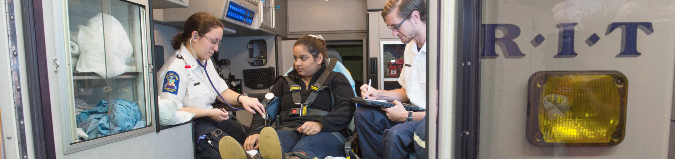 A person in the back of an ambulance with two health professionals.