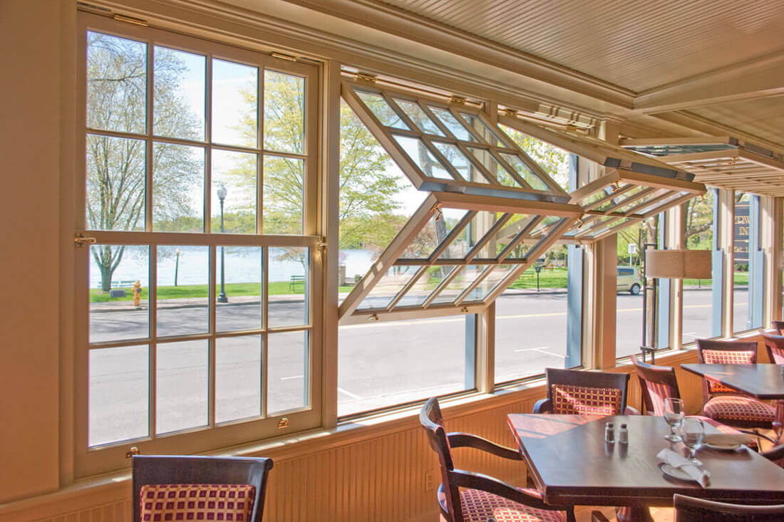 Interior of a restaurant dining room featuring folding windows from Rochester Colonial