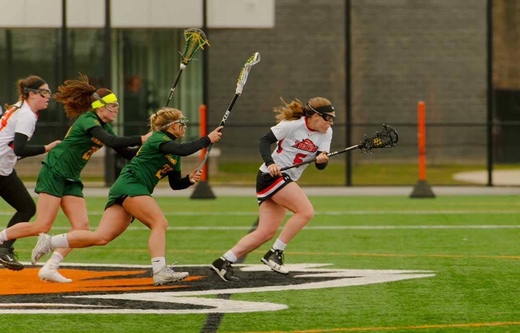 Female lacrosse player being chased down the field.