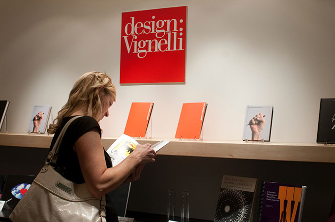 a woman browsing a book in the Vignelli collection