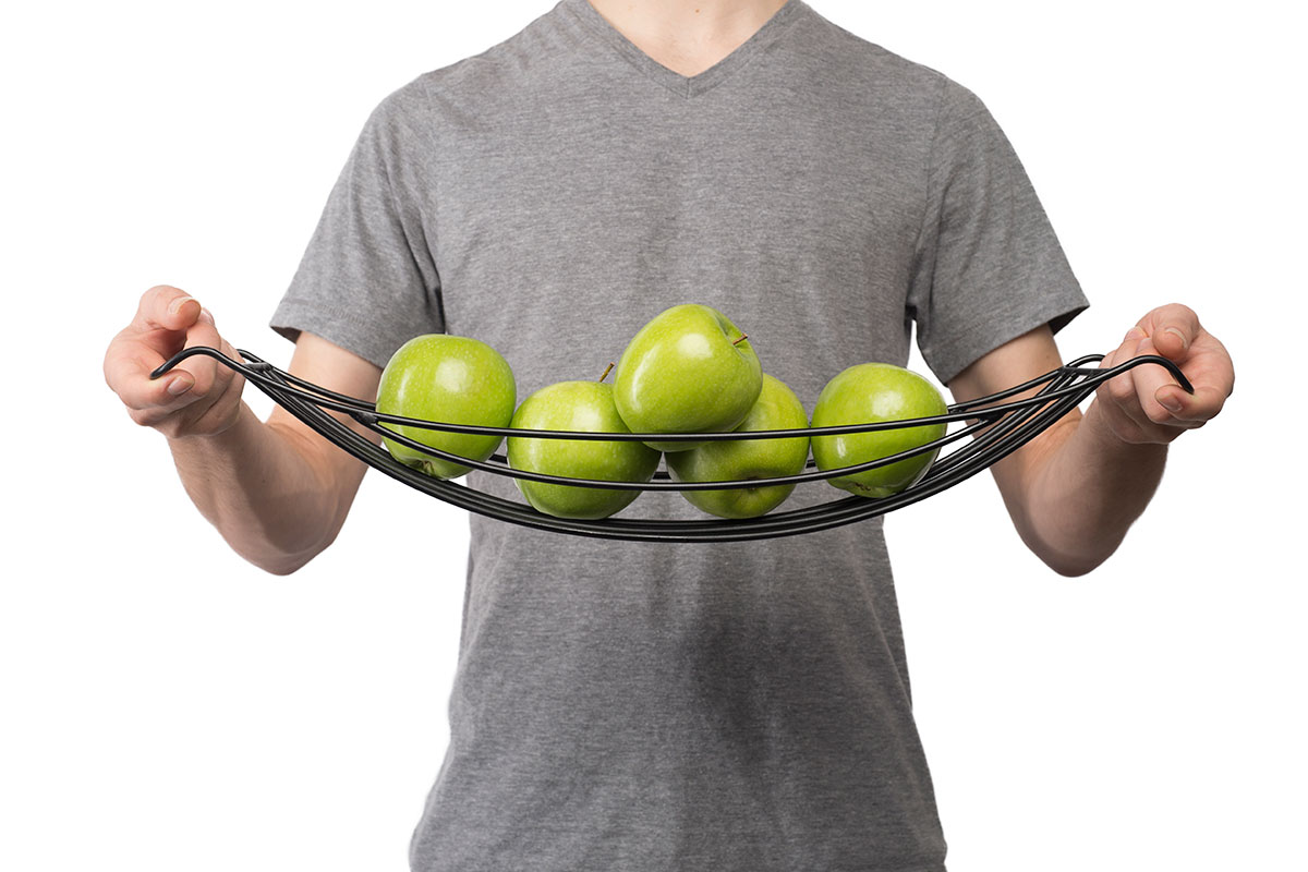 a person holding a tray of green apples