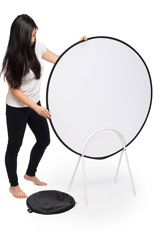 a woman holding a light filter in a metal stand