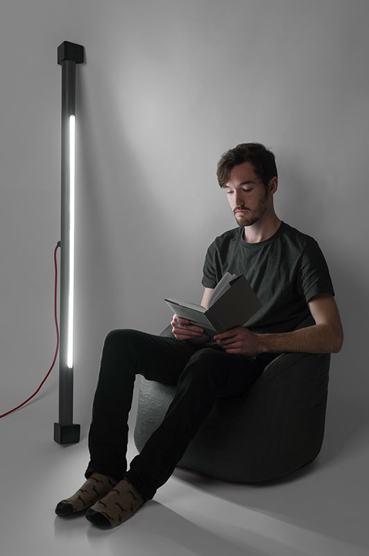 a man sitting by a tall light tube reading a book