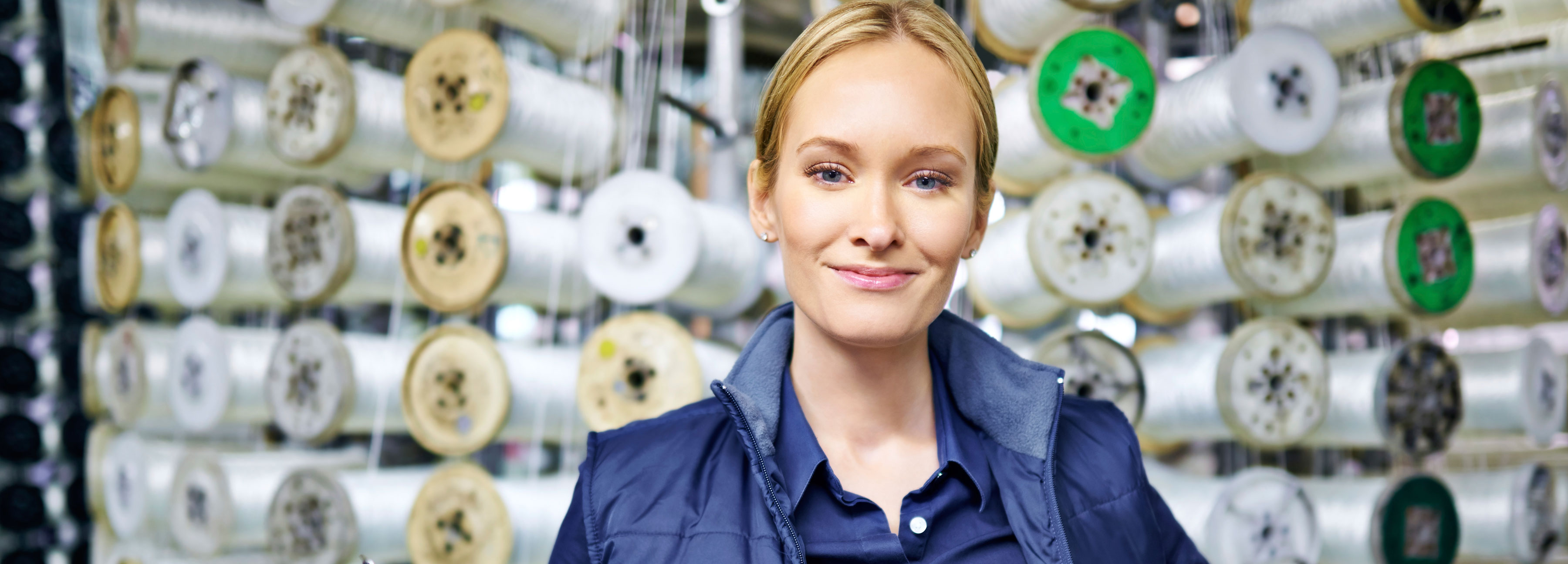 Woman standing in front of manufacturing equipment