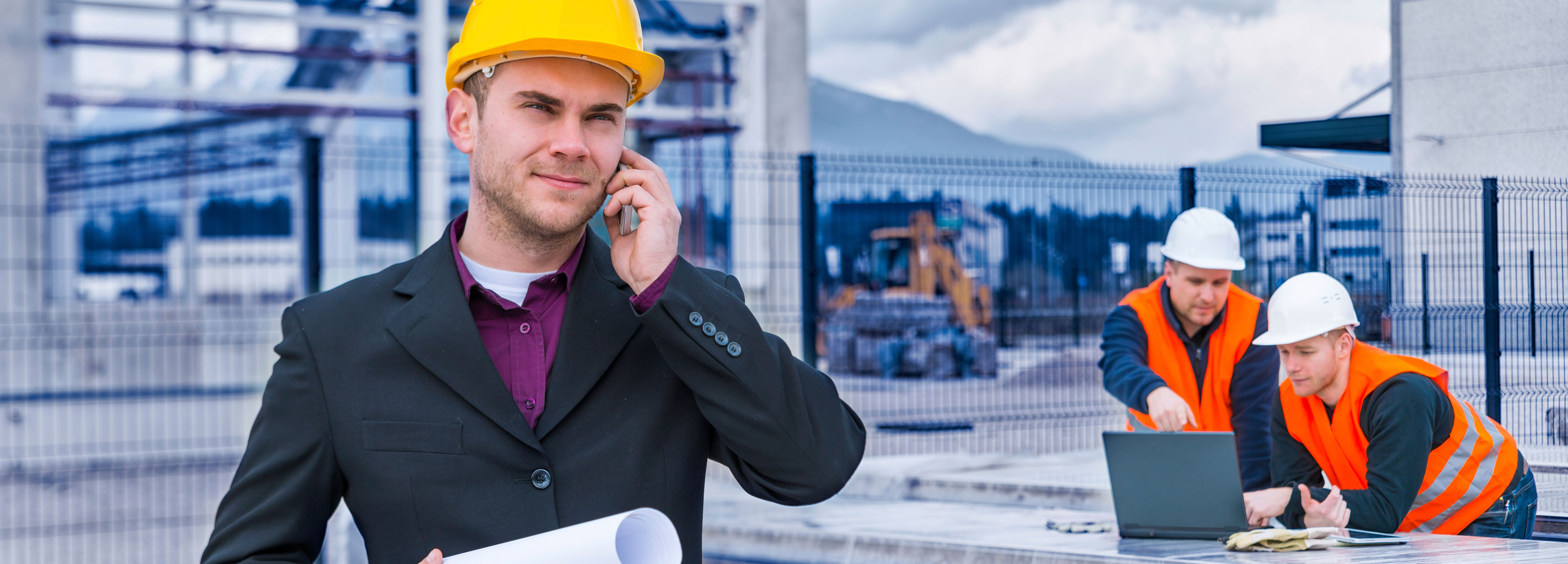 Foreman on a phone call with two construction workers in the background