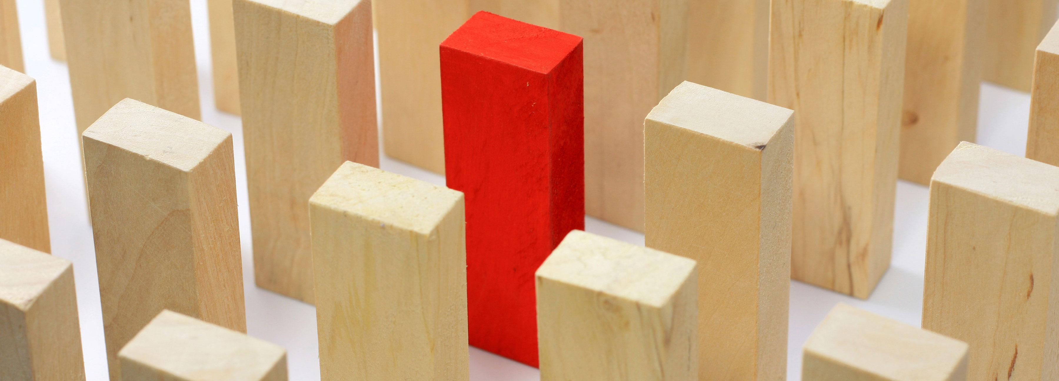 One red block among wooden blocks