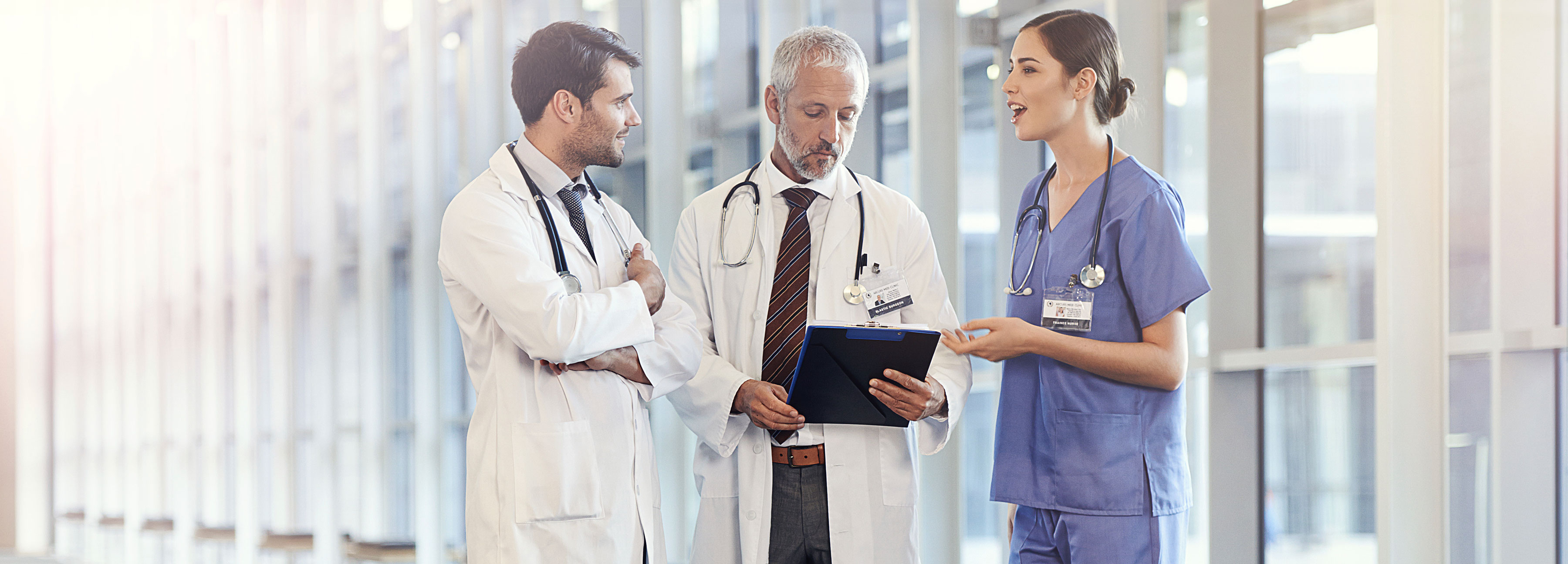 Three medical professionals reviewing charts