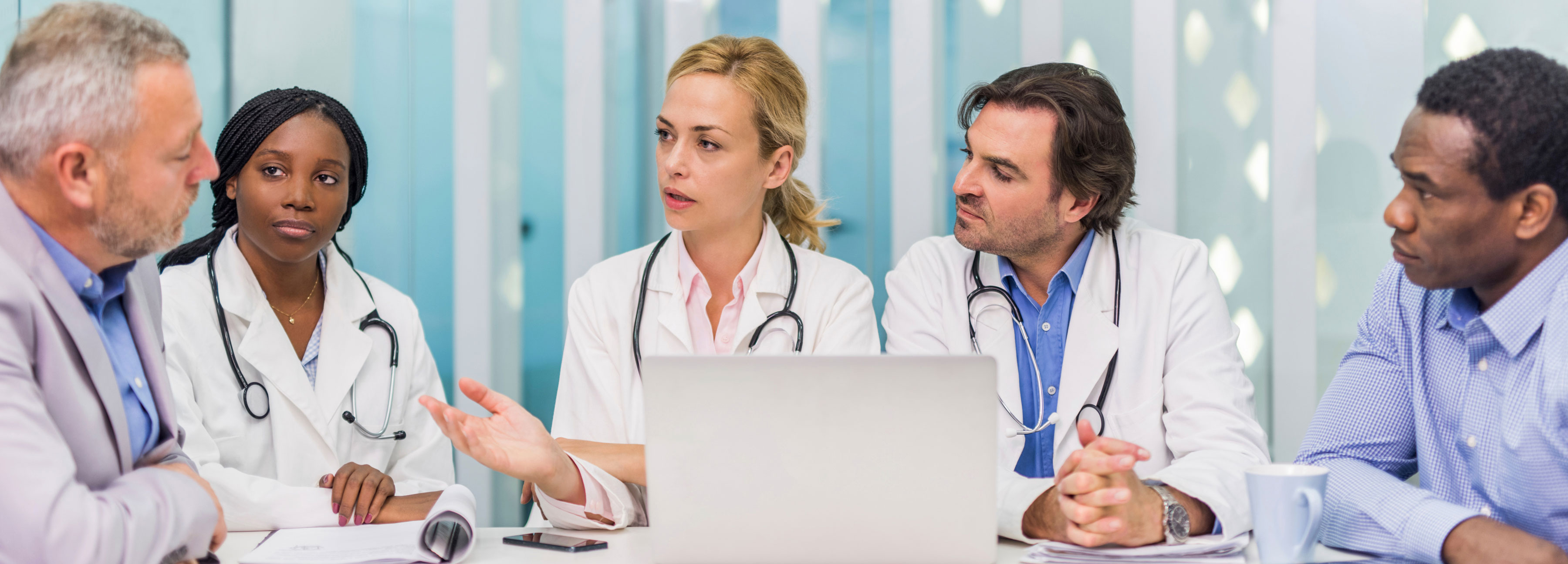 A team of medical professionals in a conference room reviewing information